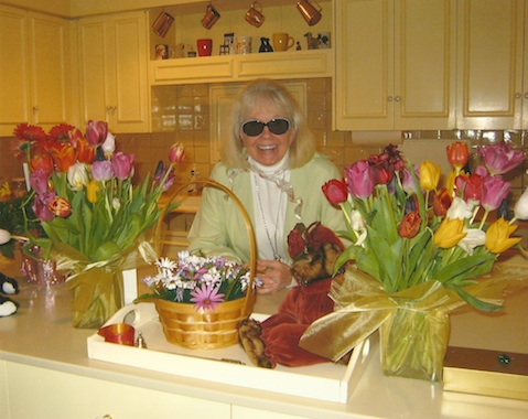 Doris in her newly decorated kitchen, surrounded by tulips from an adoring fan